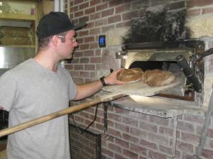 Bryn Rawlyk checks bread in his hand-built oven at The Night Oven Bakery, Saskatoon, SK